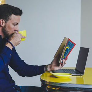 man reading while drinking coffee